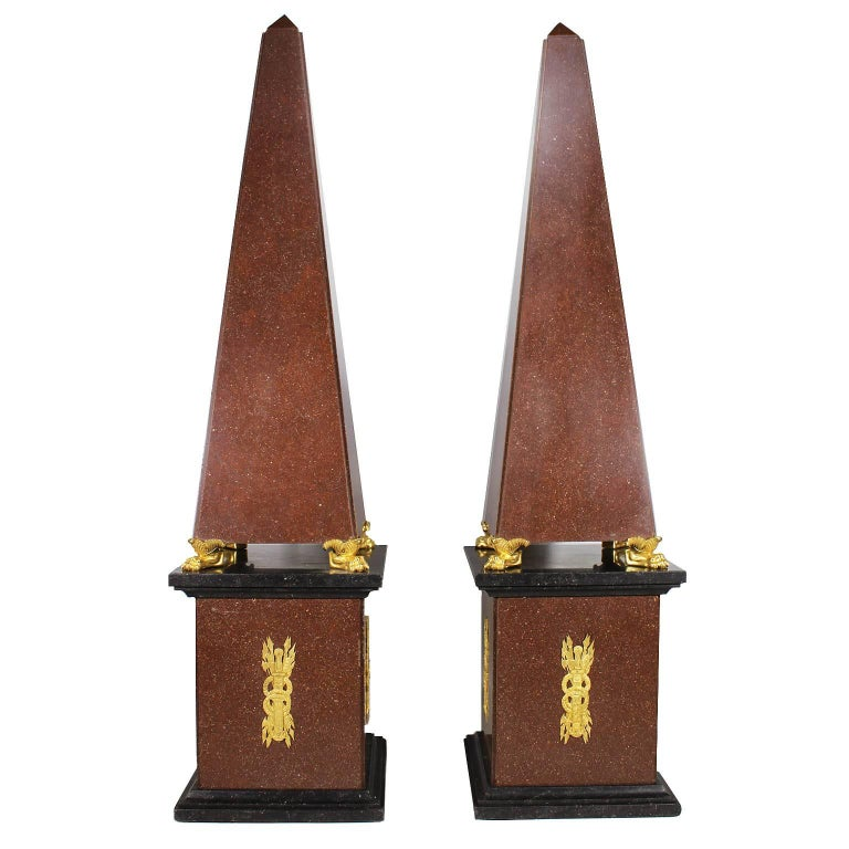 A Monumental and Fine Pair of French 19th, 20th Century Empire Style Red Porphyry and Gilt-Bronze Mounted Obelisks on Four Gilt-Bronze Lion Paws both resting on conforming porphyry and black slate plinths surmounted with allegorical Empire