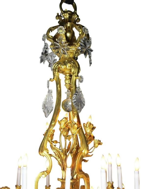 A very fine and Palatial French 19th century Louis XV style figural gilt-bronze and crystal thirty-three light chandelier, attributed to Baccarat, after a model by Jacques Caffieri (French, 1678-1755) with twenty one Candelabra Arms, three
