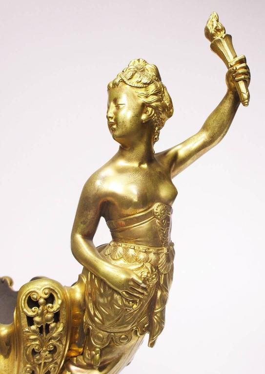 A fine and rare French Napoleon III gilt bronze trophy with a cherub and a maiden holding flame, an allegory to