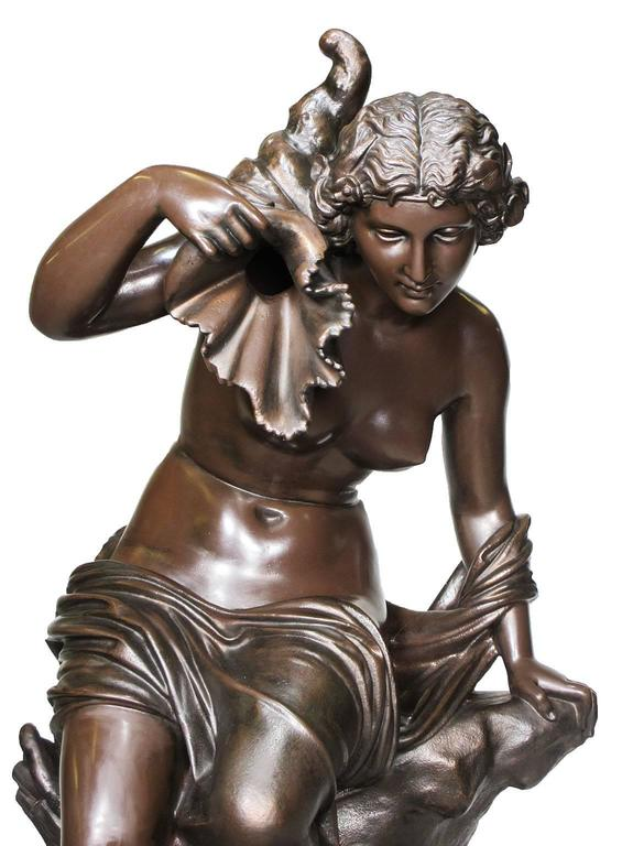 A Fine and Large French 19th Century Cast-Iron Fountain Figure Modeled as a Nude Maiden Seated on a Rocky Outcrop Holding a Cornucopia in Her Raised Right Hand, by J.J Ducel. Cast-Signed