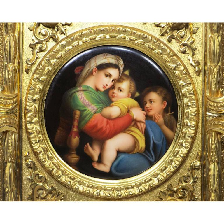 A very fine German 19th century circular porcelain plaque painting of La Madonna della Sedia after Raphael Sanzio (1483-1520), depicting a seated Madonna and child next to a child Saint John the Baptist, within a giltwood carved figural frame, the