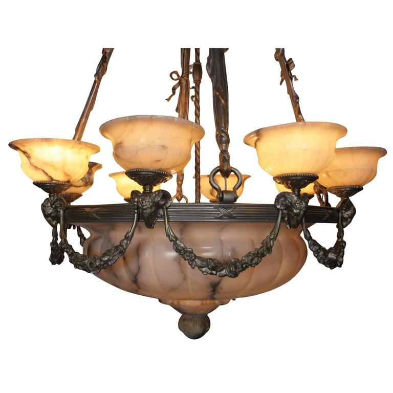 A large and rare early French 20th century Art Deco and silvered bronze carved veined cream alabaster eight-light figural chandelier. The impressive carved ovoid plafonnier with a carved finial mounted on a circular banded frame surmounted with