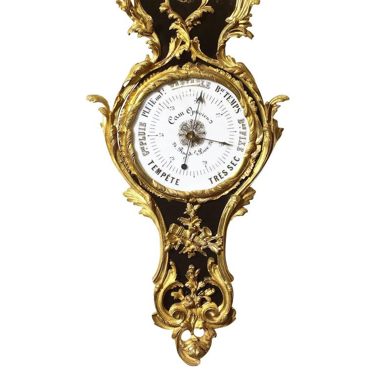 A very fine and palatial pair of French 19th- 20th century Louis XV style ebonized and gilt bronze-mounted cartel clock and matching barometer by La Maison Cam Opticien. The pair similarly surmounted with gilt bronze ornaments depicting scrolls,