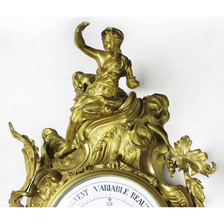 A very fine French 19th century Louis XV style gilt-bronze figural Cartel Barometer by A. Crin, A Paris. The wall mounting cartel barometer crowned with a figure of a seated maiden amongst acanthus and leaves, the circular porcelain dial with a
