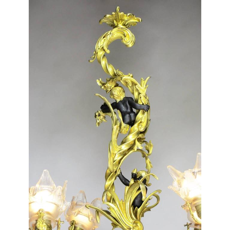 A fine French Belle Époque gilt and patinated bronze figural four-light whimsical chandelier. The scrolled gilt bronze body with branched arm lights with floral frosted glass shades, the upper stem surmounted with a pair of black-patinated bronze