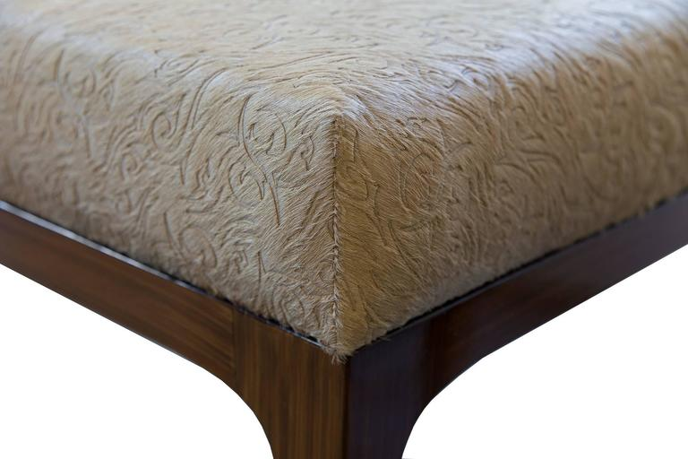 The Raphael Ottomans by KLASP home  Mid-Century Modern style laser cut floral pattern cowhide ottomans, sold as a pair.  Laser cut floral pattern cowhide in caramel Sold as a pair  Normandy cowhide Mid-Century Modern frame 90 shine Dark