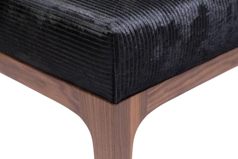 The Raphael walnut Ottomans by KLASP home. Pair of Mid-Century Modern style with a laser cut pattern black cowhide upholstered ottomans, sold as a pair. Laser cut stripe pattern cowhide in black. Sold as a pair. Normandy cowhide. Mid-Century Modern