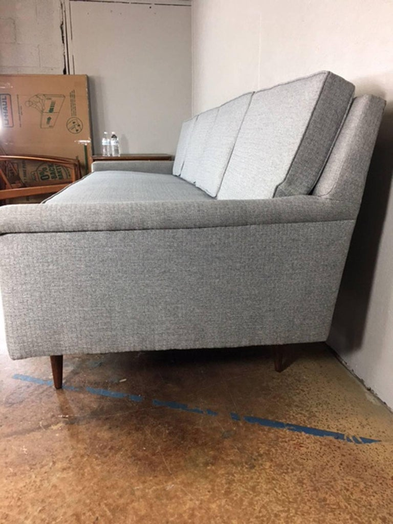 Extra long sofa by Ed Wormley, circa 1960s. Simple clean lines with walnut legs. Newly reupholstered in a sleek gray comfortable fabric.