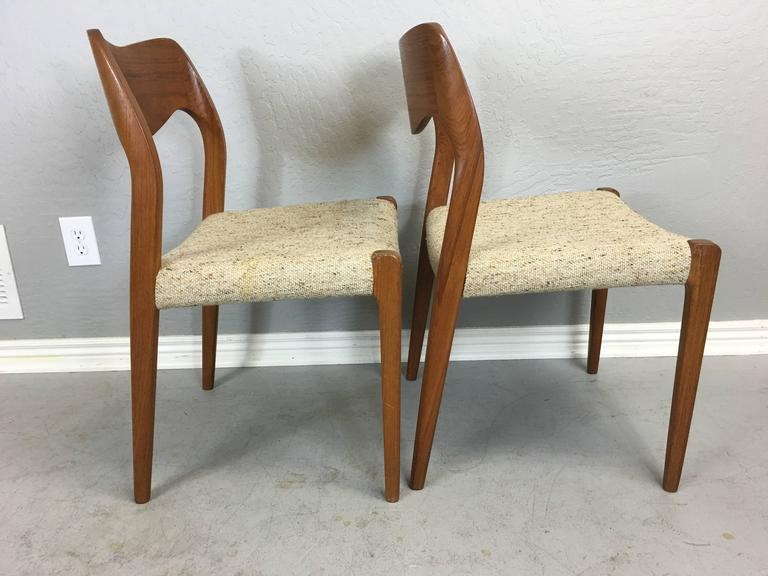 Pair of J. L. Moller teak dining chairs. Oatmeal fabric on seats is clean with no stains or rips. Makers mark on bottom.