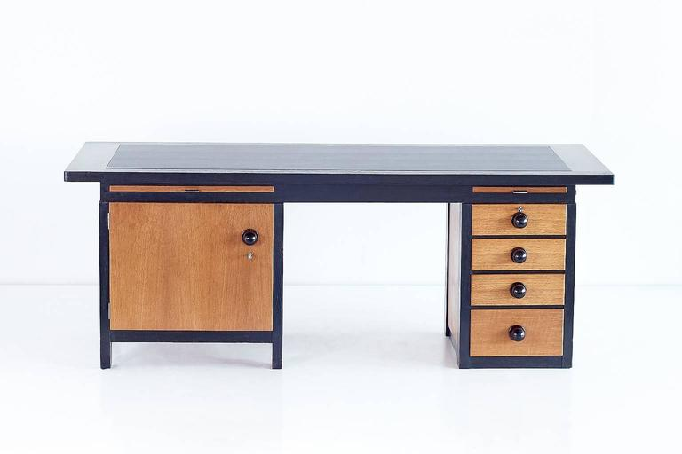 This monumental desk was designed by Frits Spanjaard in 1932. Due to its generous proportions, striking assymetry, contrasting woods and the large knobs in Macassar ebony, the desk can be considered as an important example of the Haagse School (The