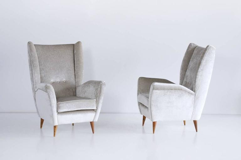 These high back armchairs were designed by Gio Ponti in the late 1940s. The chairs are characterized by their strikingly modern lines, elegantly tapered walnut legs and generous proportions.