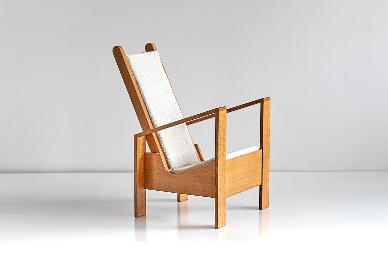 This modernist armchair was designed and produced in France in the 1940s. The architectural lines of the design are reminiscent of the work of the French designer Jean Royère. The distinguishable grain of the solid oak frame and the bouclé fabric
