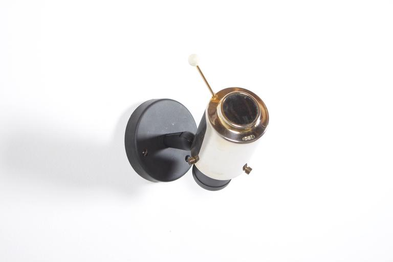 Nice wall lamp designed in the 1950s by Jacques Biny.  Manufacturer: Lita, France.  Shade: Polished brass with magnifying glass.  Wall mount: Black lacquered.  If you have any questions, please feel free to contact us.