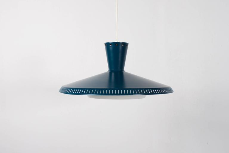Industrial Philips NB93 pendants or flush mounts in very good condition.  We have six of these lamps available.  The outside of the shade is lacquered in a beautiful petrol color.  The inside is lacquered in white and holds a white plexiglass