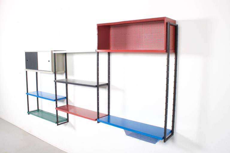 High quality metal wall unit attributed to Mathieu Mategot in very good condition.  This wall unit consists of:  Four multicolored metal shelves One perforated metal shelve  One metal shelve with a perforated  One two-door cabinet  One perforated