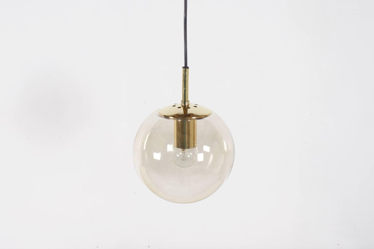 Glashütte Limburg pendants in beautiful condition.   Brass hardware.   Handblown clear glass globes which give a warm light effect, 25 cm in diameter   Black cord and canopy.    The length of the cord can be customized for free.   Marked: