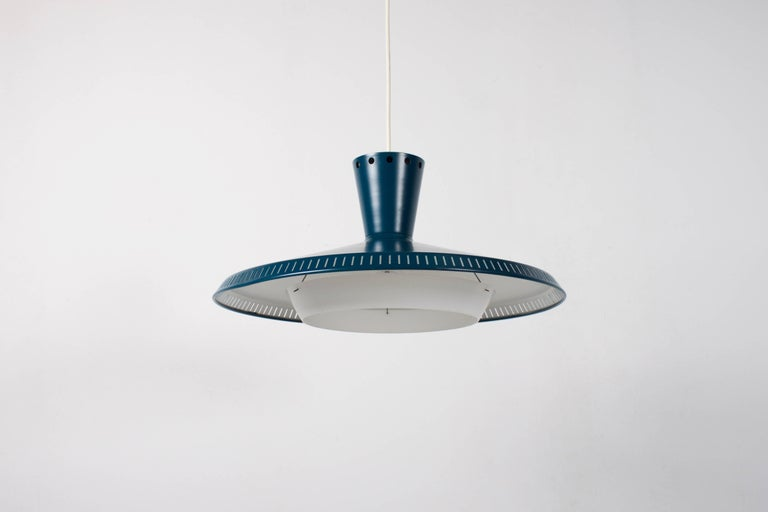 Industrial Philips NB93 pendants or flush mounts in very good condition.  We have ten of these lamps available.  The outside of the shade is lacquered in a beautiful petrol color.  The inside is lacquered in white and holds a white plexiglass