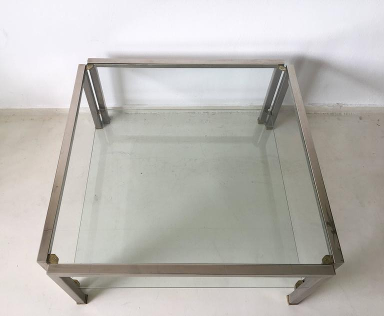 This glass coffee table with two shelves, was designed and manufactured by Peter Ghyczy in the Netherlands in 1986. It's frame is fabricated in 3x3 cm stainless steel square tubing fastened together with with brass and ribbed fittings. The glass top