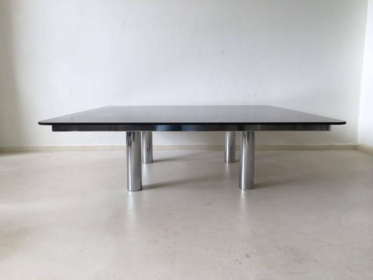 This edition of the André coffee table was designed by Tobia Scarpa for Gavina/Knoll in the 1960s. It features a smoked table top set on a chromed base with leather inlay on top. It remains in a good vintage condition with some small scratches and