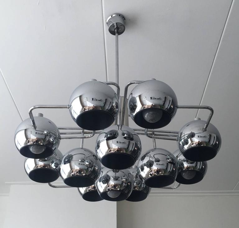 This stunning lamp comes with 12 chrome globe's attached to a geometric base. It's design can be attributed to Sciolari and was manufactured in Belgium by Boulanger, circa 1960s. This piece remains in a very good vintage condition, with wear