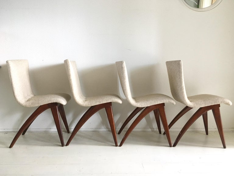Wonderful sculptural set consisting of four chairs with brown lacquered wooden legs and a flexible, comfortable seating upholstered with off-white/cream colored fabric. All of the chairs remain in very good and sturdy however one chair has a small