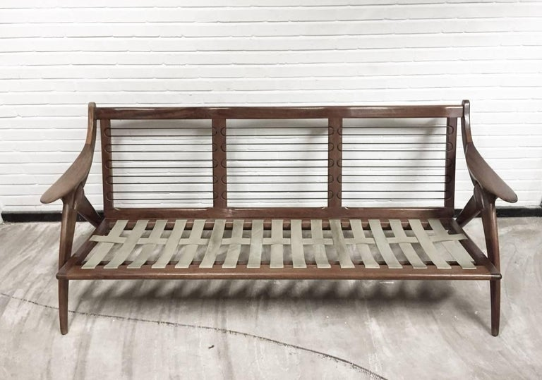 This midcentury sofa was manufactured by De Ster Gelderland in The Netherlands. It has an organic-shaped massive wooden frame and original off-white upholstery which best can be renewed. Also it's foam and singles are best to be replaced.