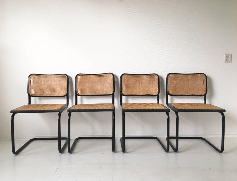 These four iconic chairs were designed and manufactured in Italy, circa 1970s. They feature a black tubular base with caned seats and backrests. The chairs remain in a very good and sturdy vintage condition and show only minimal signs of age and