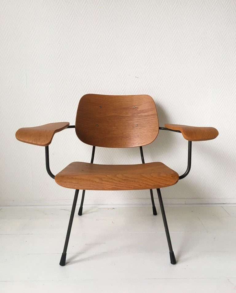 Industrial midcentury design by Tjerk Reijenga for Pilastro in 1962. The chair features a dark anthracite colored metal frame with armrests, back and seat made from teak plywood. Very good and solid condition, with some small restorations (see: