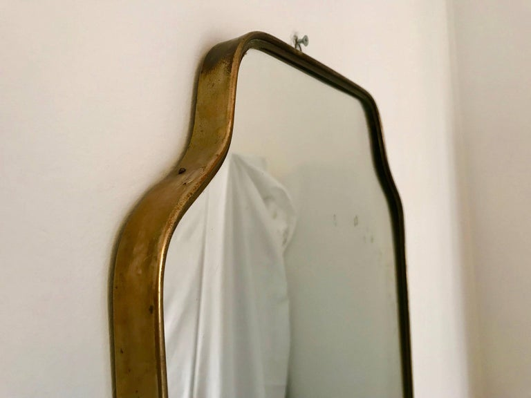 Authentic Italian Brass Mirror from the Mid Century period, original condition. The mirror presents some signs which is completely normal due to age and a direct testimony of its intact authenticity. Approx size 69h x 41 cm