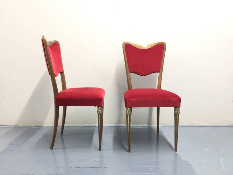 Eight Osvaldo Borsani dining room chairs brand new upholstery raspberry red velvet 100% cotton. Luxurious and really rare dining chairs with a magnificent brass ornament at front legs and curved wood back structure.   These Borsani Varedo dining