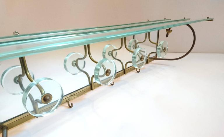 Wall hung coat rack in glass, mirror glass and brass with four glass hooks, three brass hooks as well as a glass shelf for hats etc.