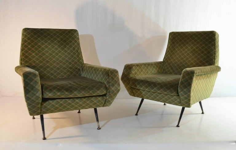 A pair of Italian armchairs in the manner of Marco Zanuso. The chairs have the original fabric and are in good condition. The legs are made from iron and has brass feet.
