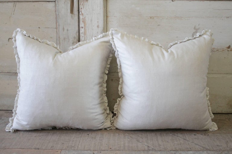 Beautiful custom-made silk pillows with a linen texture, the ruffle is 100% pure voile linen. Sewn with a hidden zipper closure, includes down/feather inserts Measures 22 x 22 100% silk is a light natural (oatmeal) color.