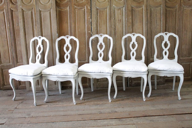 Lovely set of ten Italian carved dining chairs with cane seats, and a custom-made down cushion that we slip covered in 100% pure Belgian Linen. The slip covers have been pre washed, and have a hidden zipper closure. Each chair is solid and sturdy,