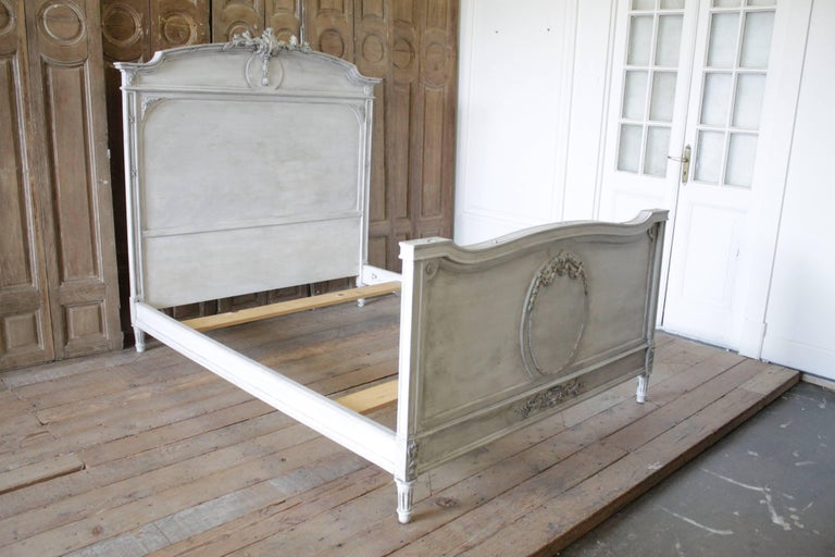 Beautiful French Louis XVI style bed painted in a soft off white, with subtle distressed edges, and hand applied patina to give the look of original painted finish. This bed frame fits a full size mattress. Includes headboard, footboard, original