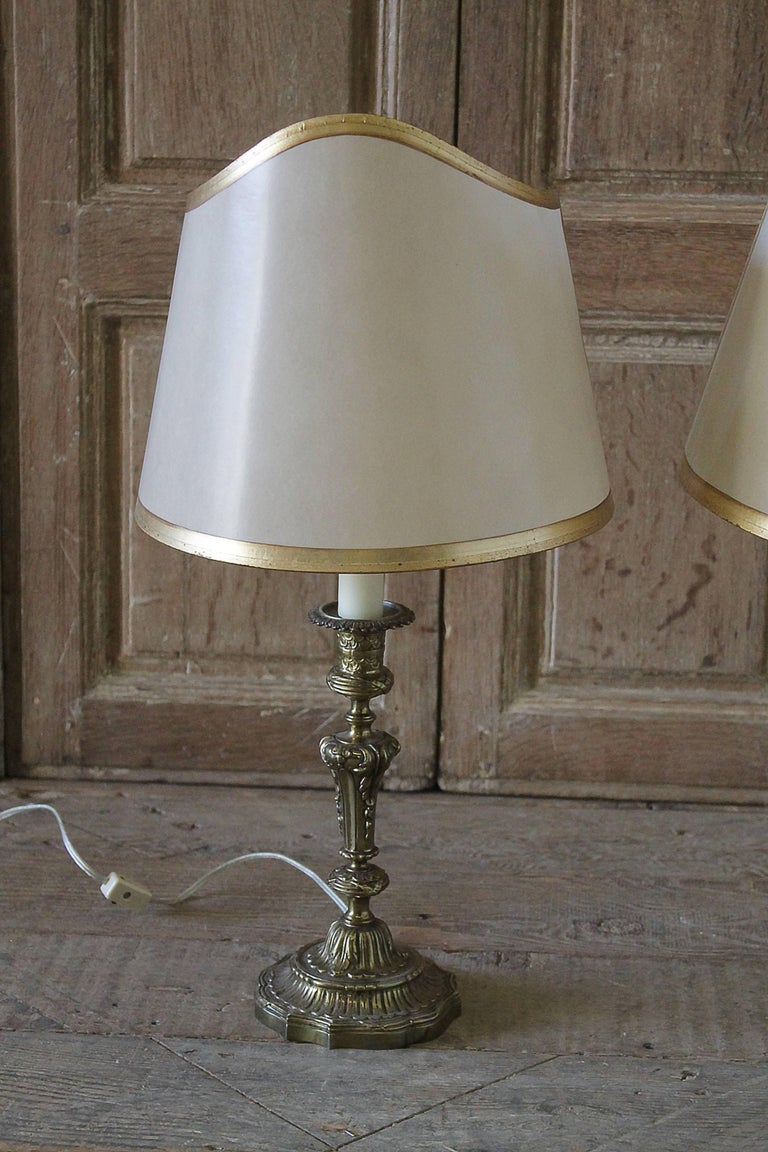 Pair of Brass Candlestick Lamps with custom parchment shades. Brass on the candlesticks have some patina, tall wax sleeves that hold a candelabra bulb. Measures with shade:  21