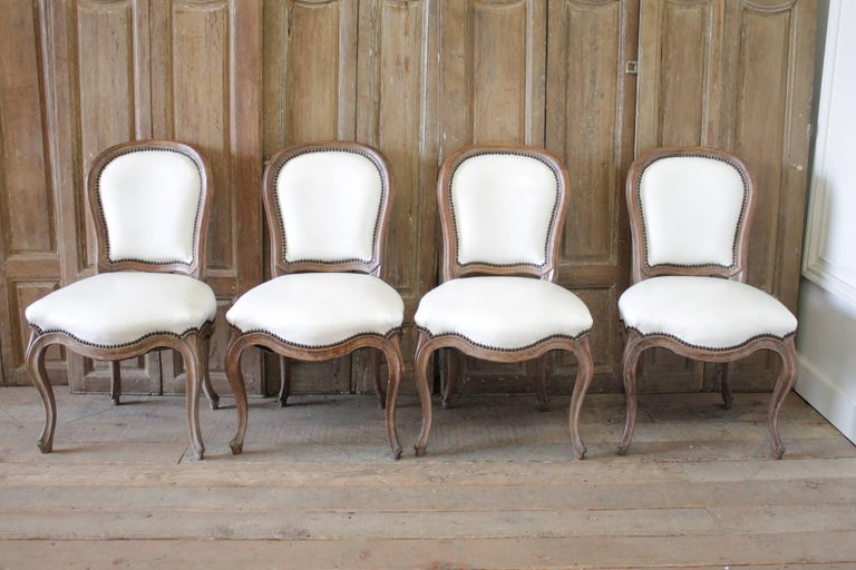 Set of ten early 20th century Louis XV style dining chairs in white leather.