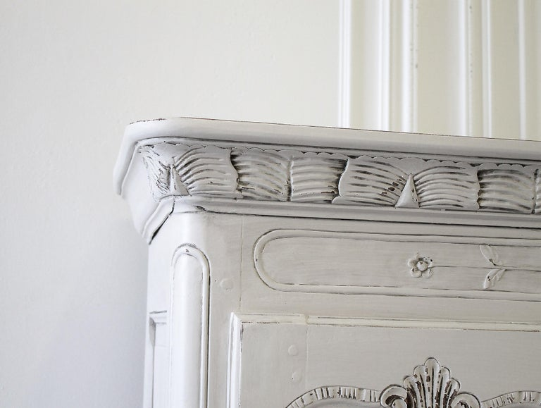 Early 19th century petite painted country French cupboard with lots of charming detailed carvings. Painted in our oyster white finish, with distressed edges, and finished with an antique glazed patina. Key and tassel are original to the piece, and