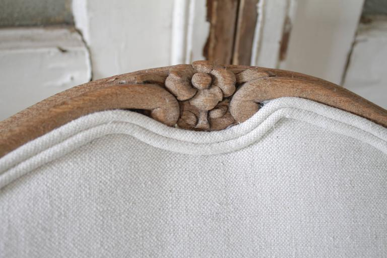Gorgeous carved walnut dining chairs with a waxed finish. Traditional Louis XV style carved legs, and upholstered in a light oatmeal color linen. The linen is a 15oz 100% pure organic Belgian linen. Each chair is very solid and sturdy, ready for