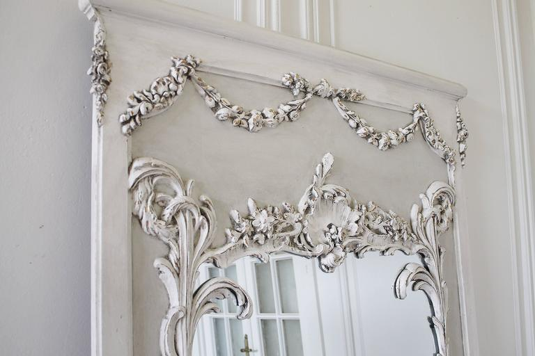 Fabulous pair of French mirrors with large carved cartouche, and floral swags, and trailing vines. Finished in our two-tone painted oyster white, with subtle distressing, and antique patina. Sold individually, these large trumeau mirrors are great
