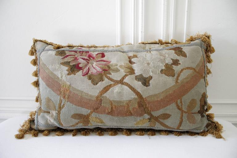 Gorgeous pair of antique pillows in a soft pale grey, tones of pale French blues, faded bronze, creams and red. Finished on the backside with a dark bronze brown velvet and trimmed with golden tassel.