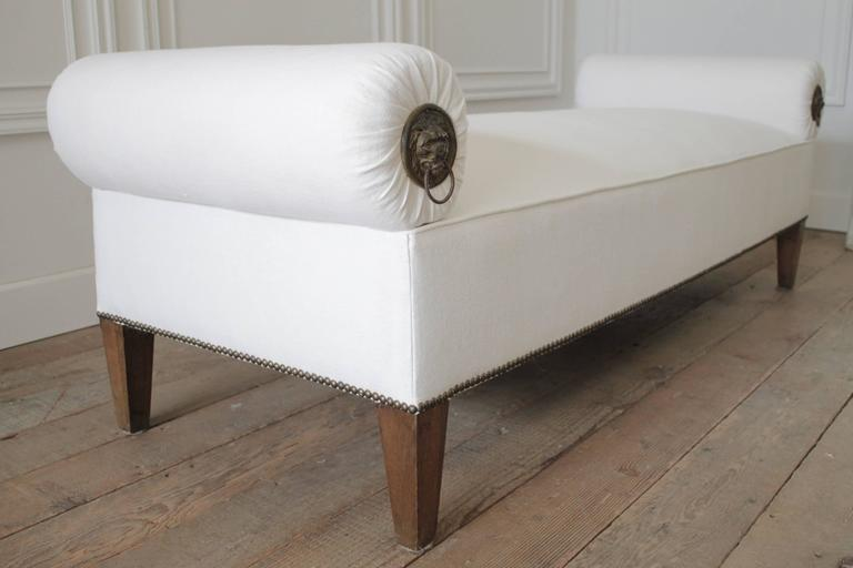 Beautiful custom designed bench with solid oak legs and antique brass nailhead trim. We reupholstered this in a soft white heavy weight Irish linen. The round bolsters feature lions head knocker hardware on one side. These bolsters are removable for