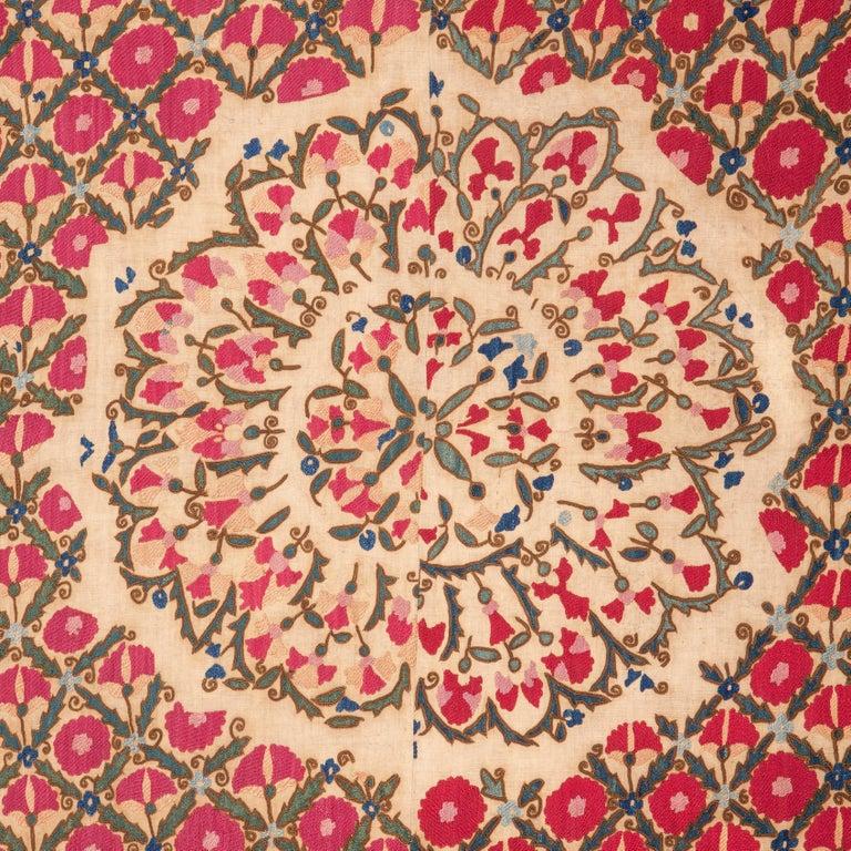 An unusual single medallion antique Suzani. Silk embroidery on cotton.