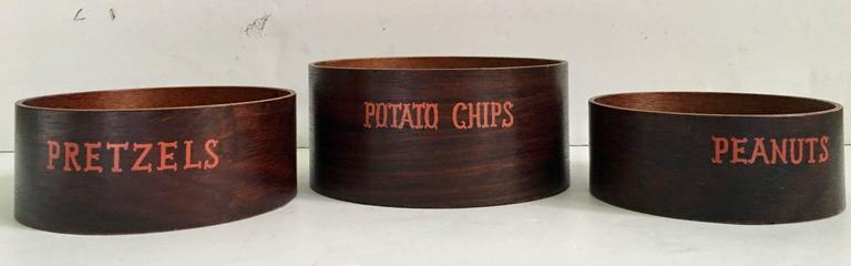 1950'S Bent teak wood nesting snack bowls. Set of three. Features bentwood teak bowls in three sizes with a printed orange motif, Potato Chips, pretzels and peanuts. Dimensions: Potato Chip: 2.75