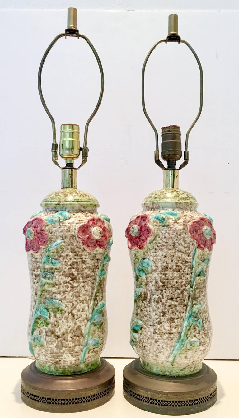 Incredible pair of ceramic glaze pottery textured and raised floral lamps. Features a white and wheat ground with floral decoration in red, pink, green white and turquoise. Original brass fittings and perforated brass base. Includes two new wheat