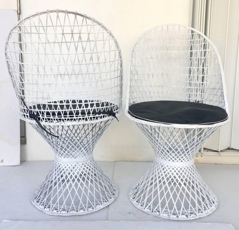 A Pair of spun fiberglass curve back chairs by Russell Woodard. Newly painted in original white finish. Includes two original black vinyl cushion with white piping. Ideal for any space, indoor or outdoor, lightweight for easy movement. Measures: