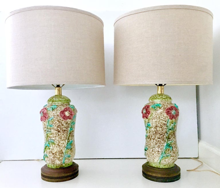 Art Nouveau Style Incredible pair of ceramic glaze pottery textured and raised floral motif  table lamps. Features a white and wheat ground with raised floral motif in red, pink, green white and turquoise. Original brass fittings and perforated