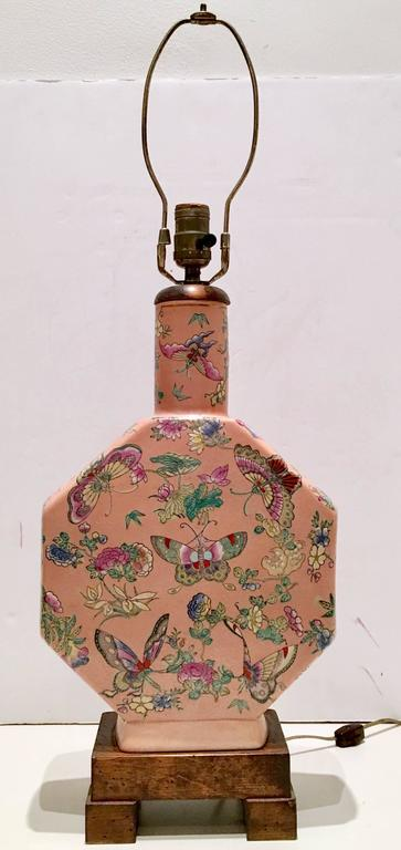 Antique Chinese Export Famille hand-painted porcelain butterfly motif hexagon lamp. Features a coral ground with multi colored butterfly motif. Burnished wood base and neck detail with 22-karat gold trim as the neck and base. Includes brass finial