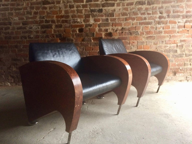 An outrageous and stunning pair of Art Deco walnut and black leather club chairs, circa 1940s, fabulous deco shaped and angled sides with chrome tube front legs and chrome bun feet to the rear, please note the leather on the chairs is in excellent
