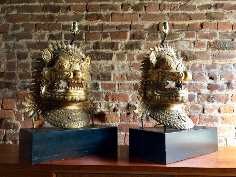 A magnificent pair of Eastern Oriental cast gilt metal side lights or table lamps modelled as dragon masks, raised on rectangular plinth bases, spectacular statement lights, large and heavy, will be the talking point of any room.  Dimensions